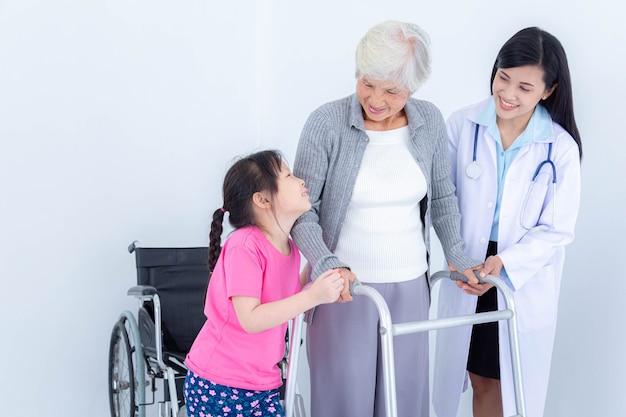 Ärztin, die älterer frau hilft, indem sie walker und ihre enkelin verwendet. altenpflege und gesundheitsversorgung, medizinisches konzept.