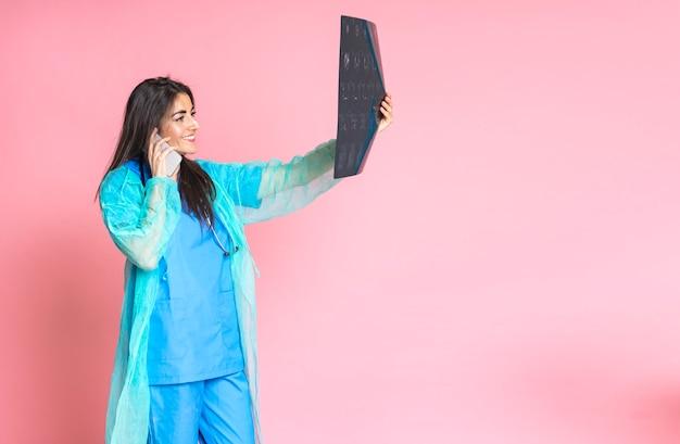 Ärztin, die am handy spricht und röntgenstrahl überprüft