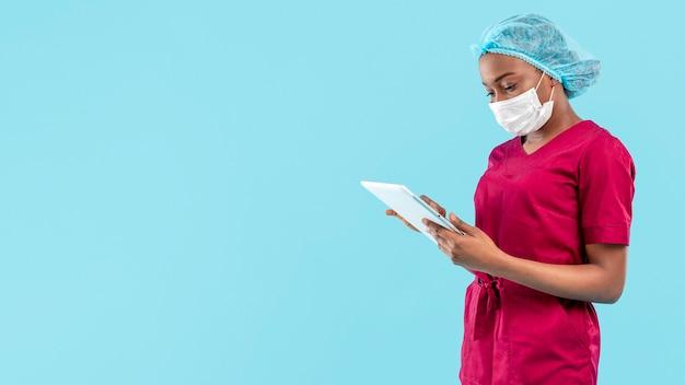 Ärztin, die an digitalem tablett arbeitet