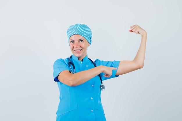 Ärztin, die auf armmuskeln in blauer uniform zeigt und selbstbewusst aussieht. vorderansicht.
