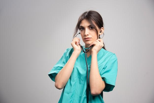 Ärztin, die auf grau aufwirft