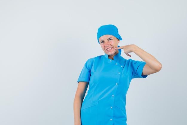 Ärztin, die auf ihr kinn in der blauen einheitlichen vorderansicht zeigt.