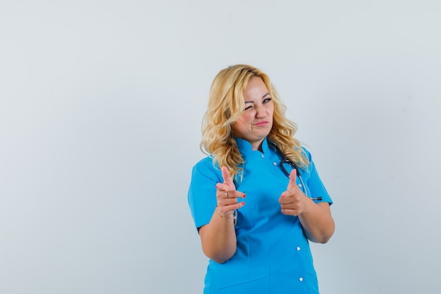 Ärztin, die auf kamera zeigt, während sie in der blauen uniform zwinkert und sicher aussieht. platz für text