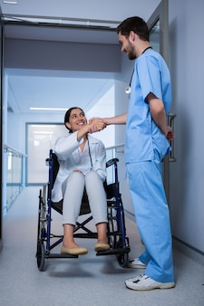 Ärztin, die auf rollstuhl sitzt und hand mit männlicher krankenschwester schüttelt