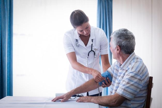 Ärztin, die blutdruck des älteren mannes überprüft