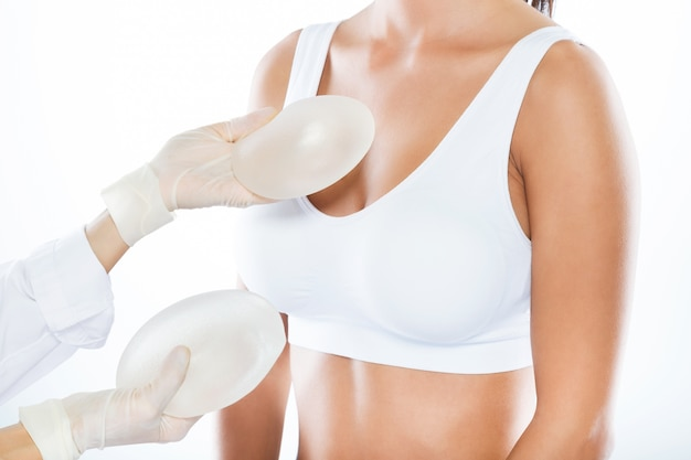 Ärztin, die brustprothese mit ihrem patienten über weißem hintergrund wählt.