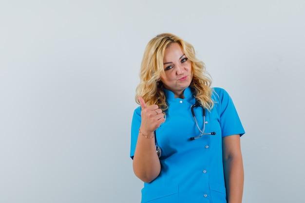 Ärztin, die daumen oben in der blauen uniform zeigt und optimistischen raum für text sucht