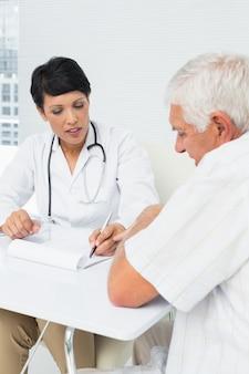Ärztin, die dem älteren patienten berichte erklärt