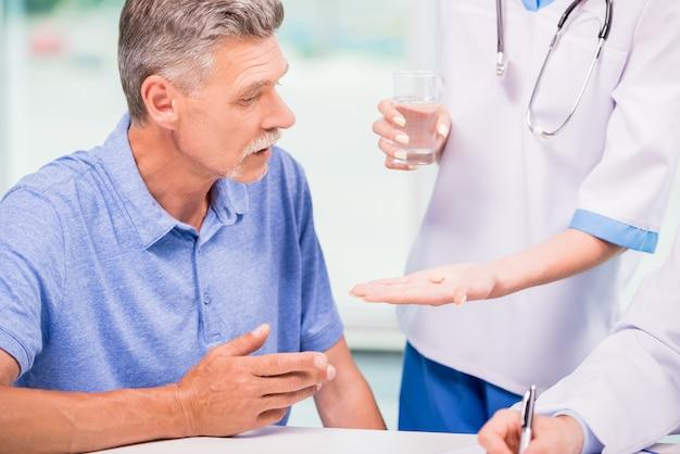 Ärztin, die dem reifen patienten eine pille gibt.
