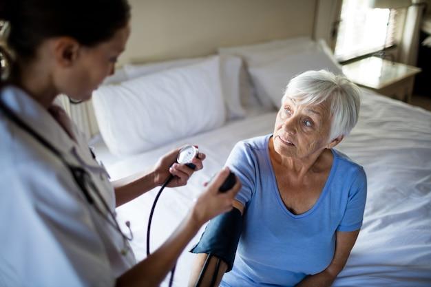 Ärztin, die den blutdruck der älteren frau im schlafzimmer zu hause überprüft
