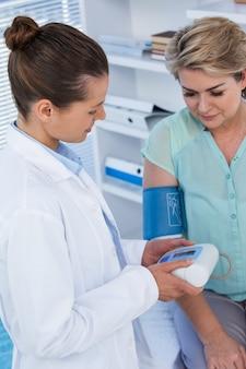 Ärztin, die den blutdruck eines patienten überprüft