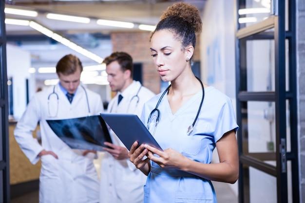 Ärztin, die digitale tablette im krankenhaus und in kollegen hinten stehen und sich besprechen betrachtet