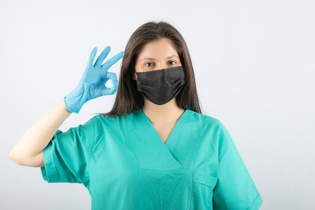 Ärztin, die eine schwarze medizinische maske trägt und eine ok geste zeigt.