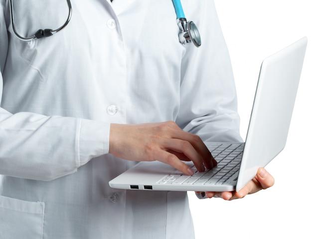 Ärztin, die einen laptop hält, lokalisiert auf weißem hintergrund