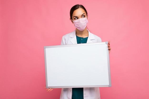 Ärztin, die einen weißen medizinischen mantel und eine maske hält, die leere tafel mit kopienraum für text hält