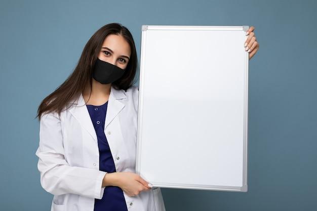Ärztin, die einen weißen medizinischen mantel und eine maske hält, die leere tafel mit kopienraum für text lokalisiert hält