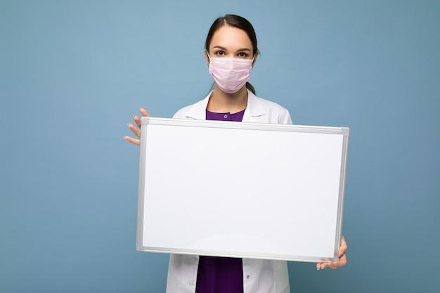 Ärztin, die einen weißen medizinischen mantel und eine maske trägt, die ein leeres brett mit kopienraum für text hält