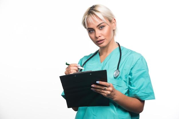 Ärztin, die etwas auf zwischenablage mit stift auf weißer oberfläche schreibt