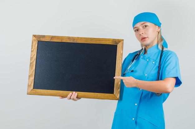 Ärztin, die finger auf tafel in blauer uniform zeigt