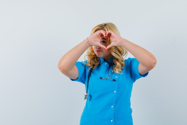 Ärztin, die friedensgeste über auge in blauer uniform zeigt und geliebt aussieht