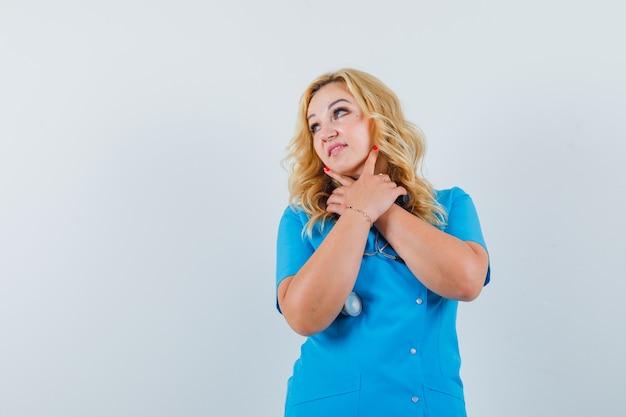 Ärztin, die hände an ihrem hals hält, während sie im blauen einheitlichen raum für text beiseite schaut