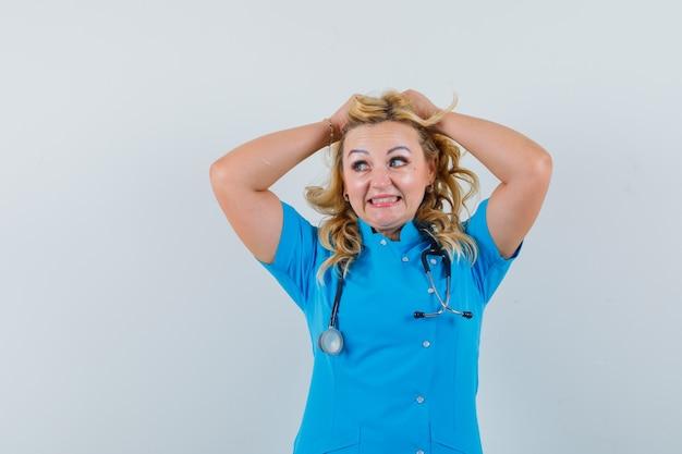 Ärztin, die hände auf kopf in blauer uniform hält und energisch aussieht.