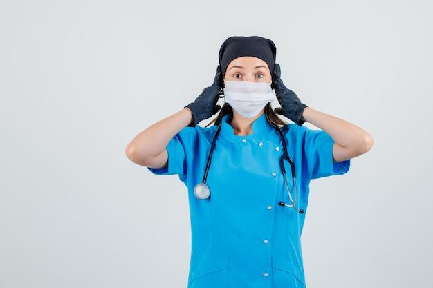 Ärztin, die hände auf ohren in uniform, handschuhen, maske hält und ängstlich aussieht