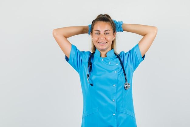 Ärztin, die hände hinter kopf in blauer uniform hält