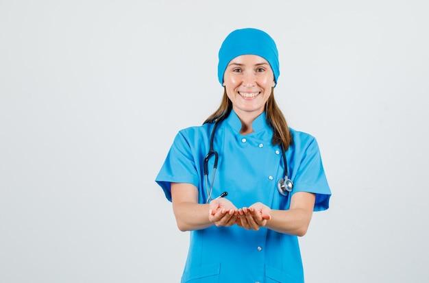 Ärztin, die hände in hohlen form in blauer uniform hält und fröhlich aussieht. vorderansicht.