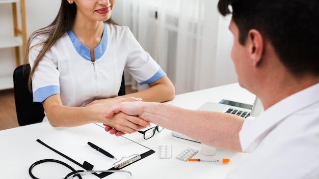 Ärztin, die hände mit patienten rüttelt