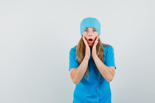 Ärztin, die hände nahe offenem mund in blauer uniform hält und schockiert aussieht