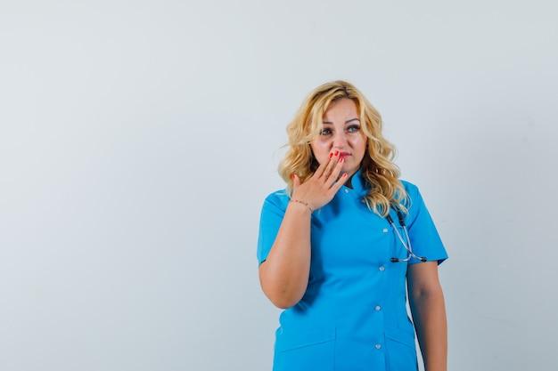 Ärztin, die hand auf ihrer lippe in der blauen uniform hält und verärgert aussieht. platz für text