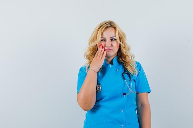 Ärztin, die hand auf ihrer wange hält, während sie in blauer uniform zur seite schaut und unzufrieden aussieht. platz für text