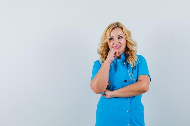 Ärztin, die hand auf kiefer in blauer uniform hält und nachdenklich schaut, raum für text