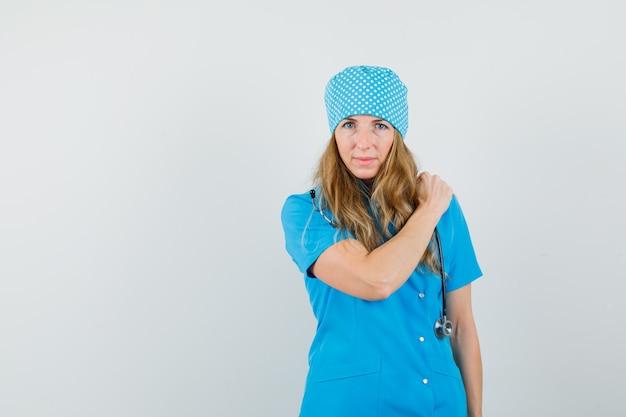 Ärztin, die hand auf schulterschmerzen in der blauen uniform hält