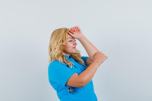 Ärztin, die hand auf stirn in blauer uniform hält und entspannt schaut.