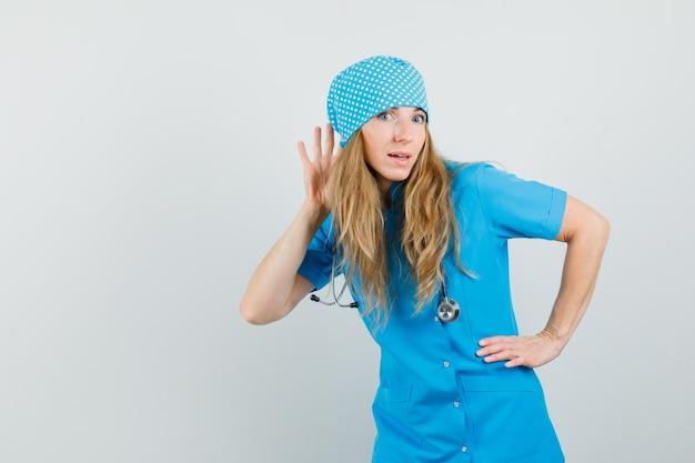 Ärztin, die hand hinter ohr hält, um in der blauen uniform zu hören und neugierig zu schauen