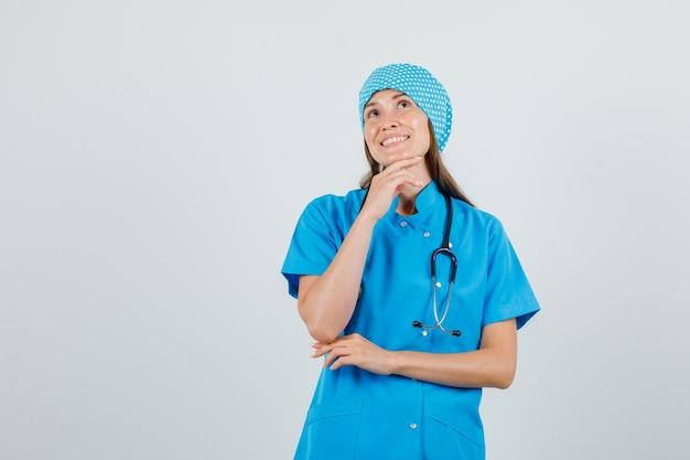 Ärztin, die hand setzt, während sie auf kinn in blauer uniform stützt und fröhlich aussieht. vorderansicht.