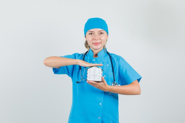 Ärztin, die hausmodell hält und in der blauen uniform lächelt