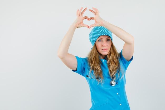 Ärztin, die herzgeste in der blauen uniform zeigt und fröhlich schaut.
