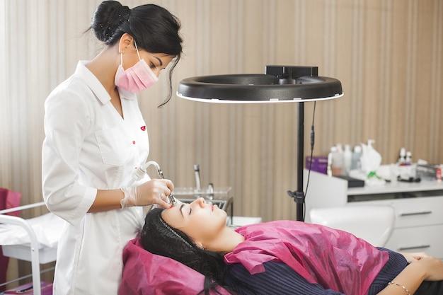 Ärztin, die ihrer patientin eine mikrodembrasion vorsieht. gesichtspflege. kosmetikerin, die geräte schält, peeling. schließen sie noch von der hautbehandlung in der schönheitsklinik oder im salon.