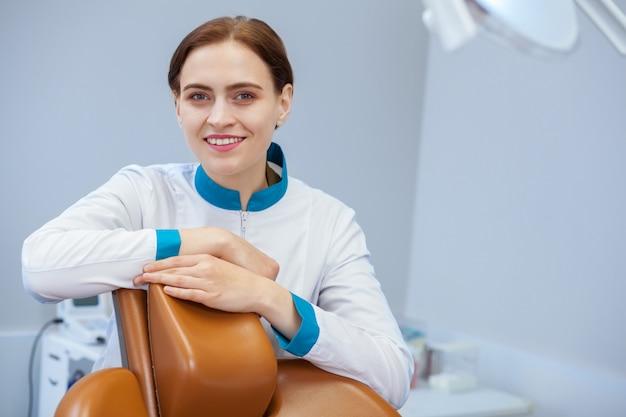 Ärztin, die im zahnmedizinischen büro, froh lächelnd zur kamera aufwirft