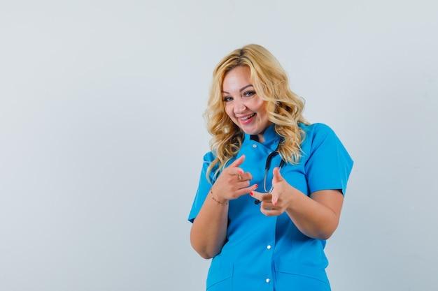 Ärztin, die in blauer uniform auf kamera zeigt und amüsiert aussieht. platz für text