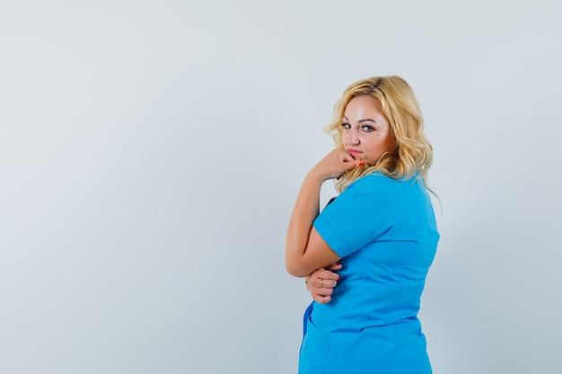 Ärztin, die in blauer uniform beiseite schaut und nachdenklich aussieht. . platz für text