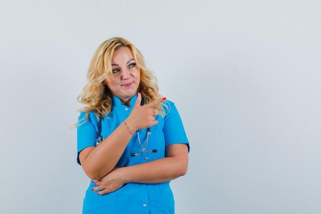 Ärztin, die in blauer uniform beiseite zeigt und fokussierten raum für text sucht