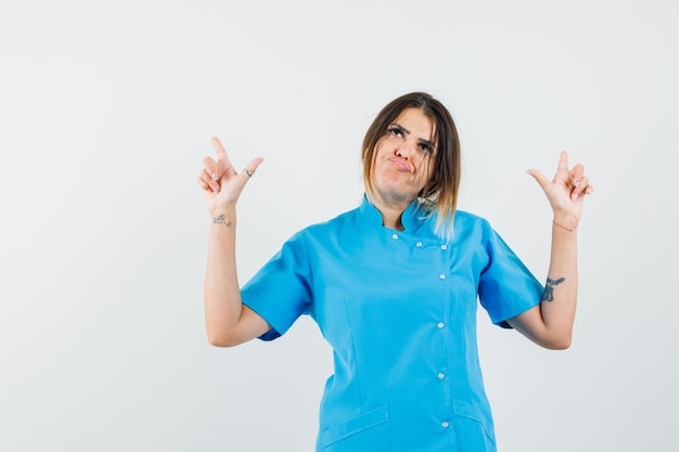 Ärztin, die in blauer uniform nach oben zeigt und hoffnungslos aussieht