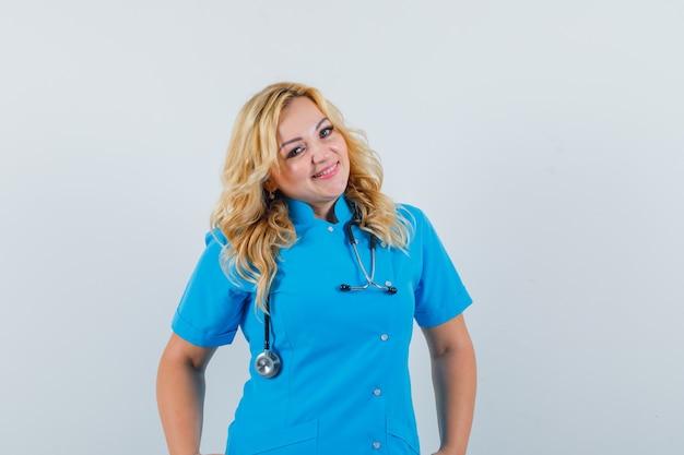 Ärztin, die in der blauen uniform lächelt und fröhlich schaut