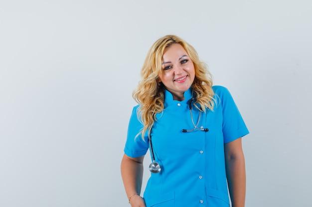 Ärztin, die in der blauen uniform lächelt und glückselig aussieht. platz für text