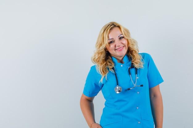 Ärztin, die kamera beim lächeln in der blauen uniform betrachtet und froh schaut.