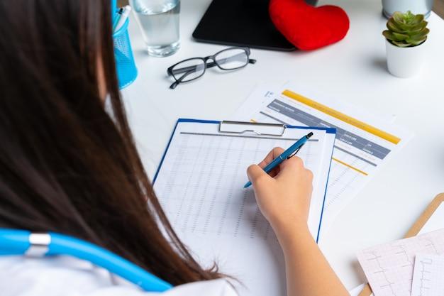 Ärztin, die kenntnisse über klemmbrett beim sitzen an ihrem tisch im büro nimmt